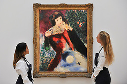 """© Licensed to London News Pictures. 06/10/2017. London, UK. A staff members view """"Les Amoureux"""", 1928, by Marc Chagall at a preview at Sotheby's in New Bond Street of contemporary, impressionist and modern art works to be auctioned in New York in November 2017 Photo credit : Stephen Chung/LNP"""