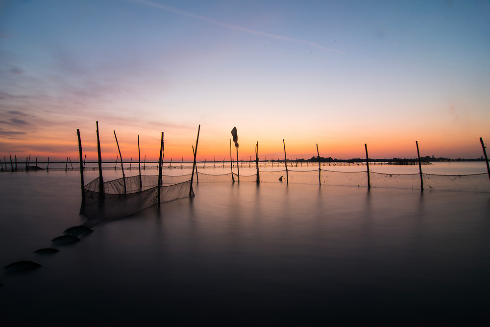 VENICE, ITALY - APRIL 2018. <br /> The fishing nets are handmade by the fishermen, and placed in areas that are assigned every year with a lottery. Everyone accept their fate, knowing that it will change every year. Sometimes it is close to the city of Venice, sometimes far away, out in the lagoon.