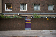 A brighlty coloured purple gate and brick block of flats on Somerleyton Road on 29th July in South London, United Kingdom