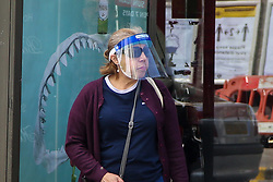© Licensed to London News Pictures. 18/05/2020. London, UK. A woman wearing a visor waits at a bus stop in north London. Passengers travelling on public transport are are asked to wear a face covering. Photo credit: Dinendra Haria/LNP