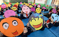 November 20, 2018 - Handan, China - Pupils draw paintings of smiling faces at a primary school in Handan, north China's Hebei Province, marking the World Hello Day. The World Hello Day was begun in response to the conflict between Egypt and Israel in the Fall of 1973.  Since then, World Hello Day has been observed by people in 180 countries. (Credit Image: © SIPA Asia via ZUMA Wire)