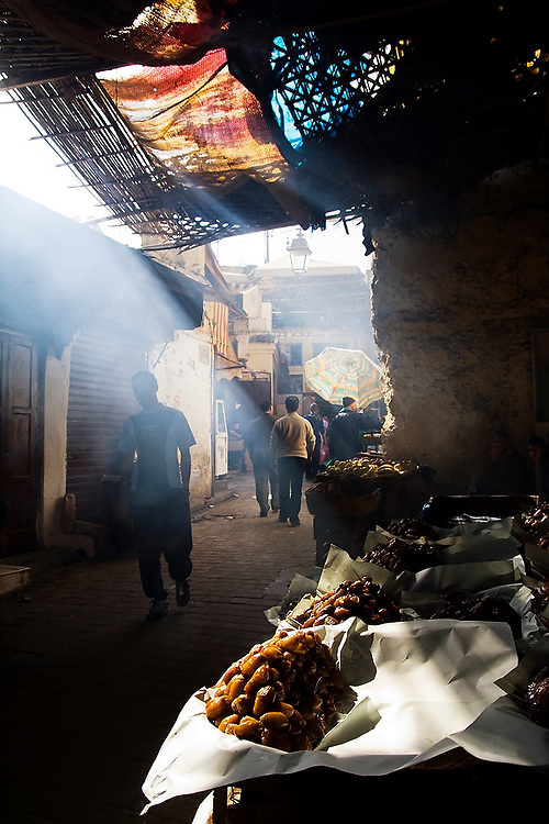 A shaft of light illuminates piles of large dried dates on sale at a street stall in a dark, busy street in Fes El-Bali, Morocco, on October 31, 2007.