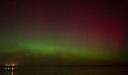 © Licensed to London News Pictures. 27/02/2014<br /> <br /> Saltburn, England<br /> <br /> The Aurora Borealis is visible out over the North sea from Saltburn by the Sea in Cleveland as ships make their way into Teesport.<br /> <br /> Photo credit : Ian Forsyth/LNP