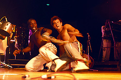 Johnny Clegg and a fellow performer getting down on stage( performing) with his band Savuka. <br /> ©Eric  Miller