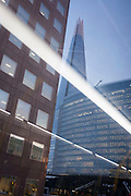 A scene of urban architecture at London Bridge with the Shard tower rising high above, and with diagonal lighting from the interior of a bus, on 9th December 2016, in the City of London.