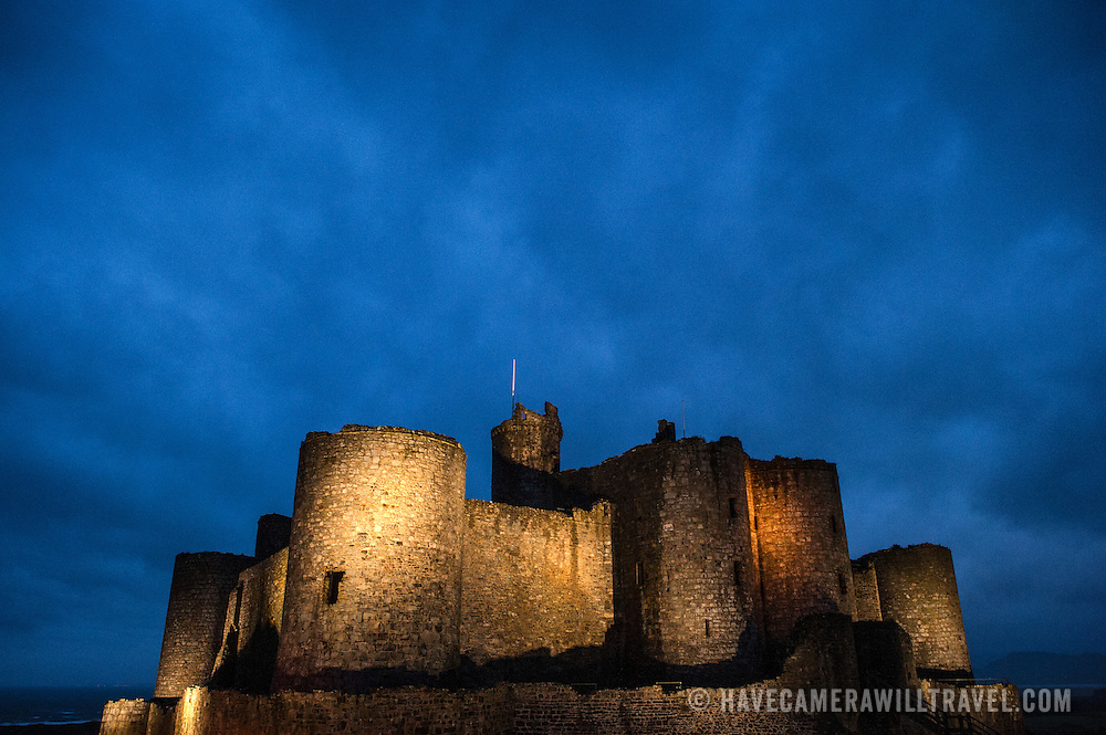 Dusk skies and lights at Harlech Castle in Harlech, Gwynedd, on the northwest coast of Wales next to the Irish Sea. The castle was built by Edward I in the closing decades of the 13th century as one of several castles designed to consolidate his conquest of Wales.
