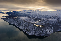 The thousand foot cliffs of White Thunder Ridge are reflected in the Muir Inlet located in Glacier Bay National Park and Preserve in southeast Alaska. This aerial view, taken in early November after a snow storm, is looking south, down the Muir Inlet (left).