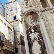 A statue of a religious figure carved into the wall of a building at the corner of a street in Split, Croatia.