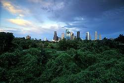Houston, Texas skyline from the west at sunset with trees in foreground.