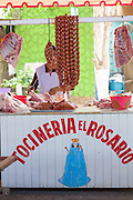 A women selling sausages and pork cuts at the Sunday market in Tlacolula de Matamoros, Mexico. The regional street market draws thousands of sellers and shoppers from throughout the Valles Centrales de Oaxaca.