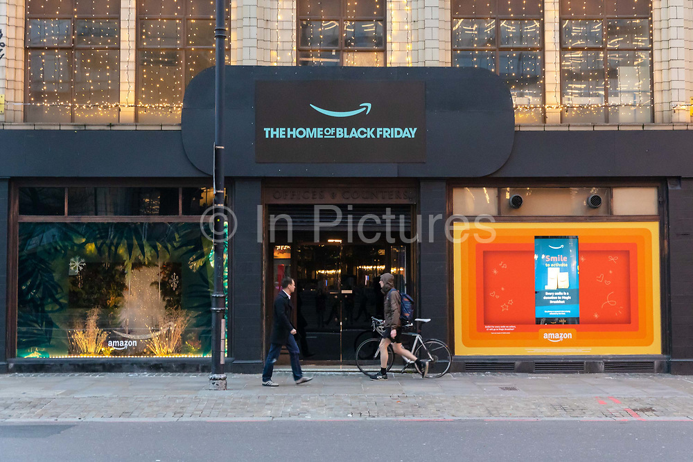 A man and a cyclist walk past  the Amazon Black Friday pop-up shop in Shoreditch, east Lonon on November 23, 2018