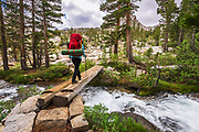 Backpacker crossing creek in the John Muir Wilderness, Sierra Nevada Mountains, California USA