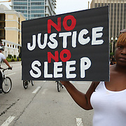 """Protesters march and hold signs in the No Justice No Peace- """"March Against Gun Violence""""  walk from Lake Eola in downtown Orlando, to the Orange County Courthouse on Wednesday, July 17, 2013. The march was organized by the Modarres Law Firm and Orlando attorney Natalie Jackson, one of the attorneys for Trayvon Martins parents. (AP Photo/Alex Menendez)"""