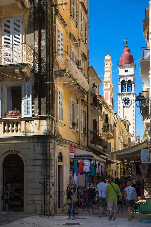 Tourists in by Spianada and Church of Saint Spyridon clock belltower, in Agiou Spiridonos Kerkyra, Corfu Town, Greece