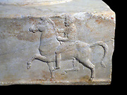Base of a dedication in  Marble.  Found in the Athenian Agora.  Base of a dedication for victories in the mock cavalry battle contest.  Three sides of it have reliefs depicting a horseman riding toward a tripod.  The inscription on the fourth side supplies the names of the victorious dedicators and also that of the sculptor Bryavis who carved the monument.  It will have supported a bronze tripod dedicated by the victors.  Middle of the 4th century BC.