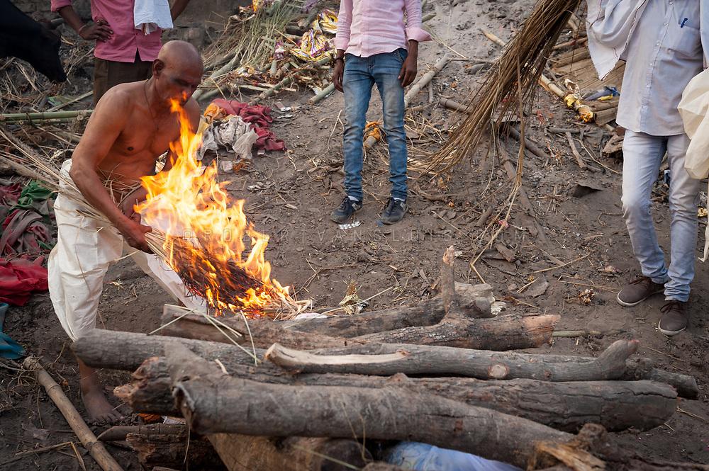 A family member lights a funeral pyre at Manikarnika cremation ground, Varanasi, India. Photo © robertvansluis.com