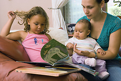 Mother reading a book with her young children,