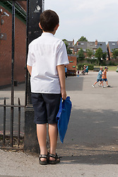 Boy at school gate looking into the playground,