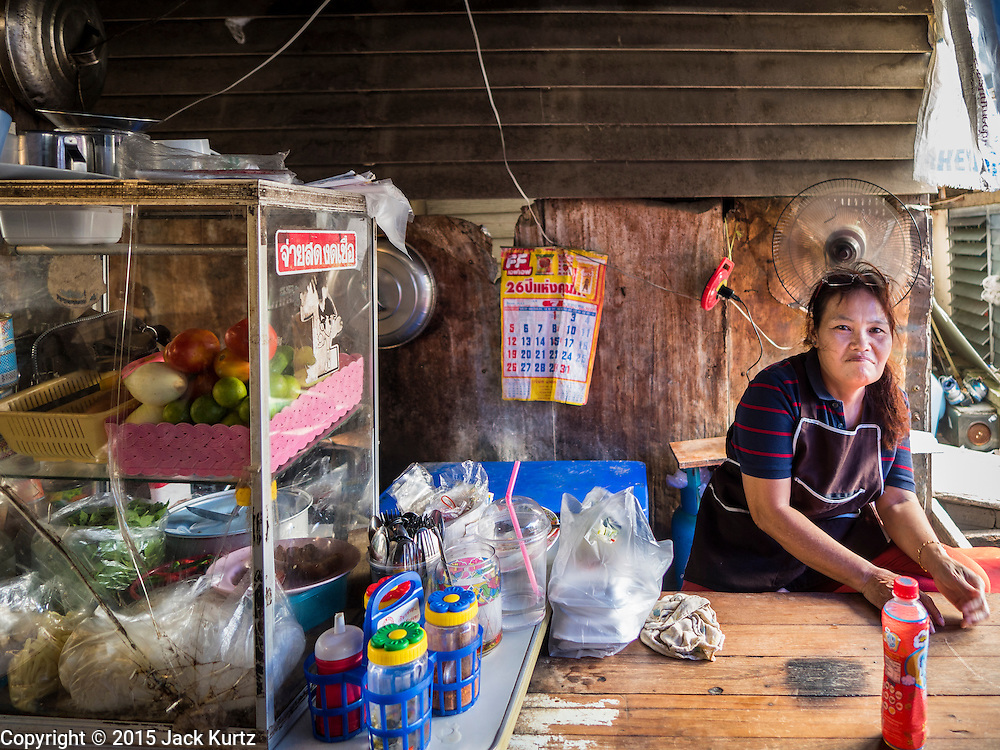22 JULY 2015 - BANGKOK, THAILAND:    A food vendor in a community on the Chao Phraya River south of Krung Thon Bridge. This is one of the first parts of the riverbank that is scheduled to be redeveloped. The communities along the river don't know what's going to happen when the redevelopment starts. The Chao Phraya promenade is development project of parks, walkways and recreational areas on the Chao Phraya River between Pin Klao and Phra Nang Klao Bridges. The 14 kilometer long promenade will cost approximately 14 billion Baht (407 million US Dollars). The project involves the forced eviction of more than 200 communities of people who live along the river, a dozen riverfront  temples, several schools, and privately-owned piers on both sides of the Chao Phraya River. Construction is scheduled on the project is scheduled to start in early 2016. There has been very little public input on the planned redevelopment.           PHOTO BY JACK KURTZ