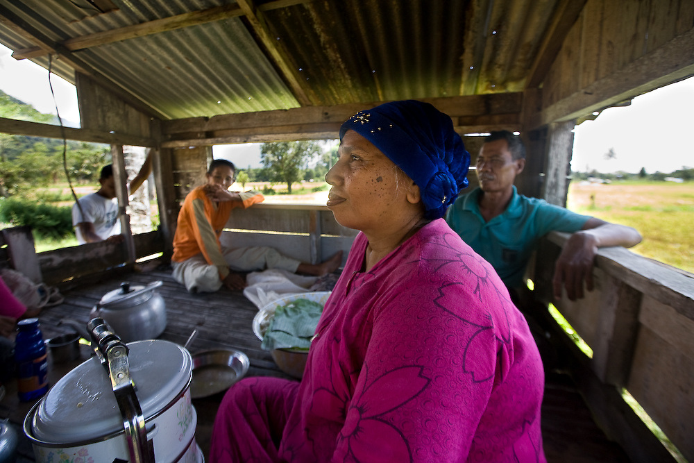 Keutapang Village near Banda Aceh - Aceh, Indonesia  Nov. 2008. (Heifer Participant)  Rurayah(left) Rubama (center), and M. Nur, a Heifer Participant (right), break for lunch from the back breaking work of harvesting rice by hand in the hot indonesia sun.