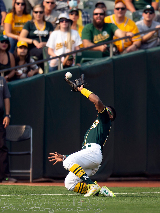 Sep 25, 2021; Oakland, California, USA; Oakland Athletics left fielder Tony Kemp (5) makes a sliding catch of a shallow popup off the bat of Houston Astros right fielder Kyle Tucker during the ninth inning at RingCentral Coliseum. Mandatory Credit: D. Ross Cameron-USA TODAY Sports
