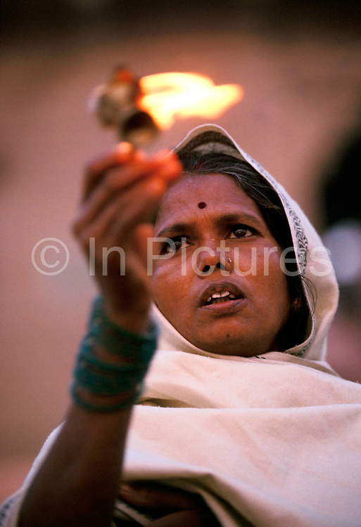 Radha, a low caste Hindu priestess, worships at the River Ganges in Varanasi, India