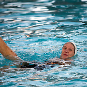 Despite having to rely on a cane and a walker to help her get around due to Multiple Sclerosis, Margo Bouer takes part in sychronized swimming at the Laguna Woods Village clubhouse pool.