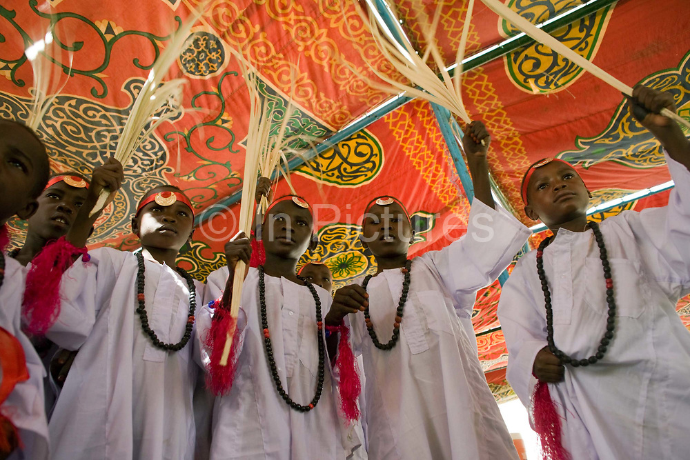 Young boys between the ages of 8 and 13 gather under the shade of a brightly-coloured canopy in the compound of the Governor of the war-torn region of north Darfur, Sudan. Dressed in white gowns and wearing red bandanas, they will soon celebrate a Sudanese rite of passage, the male circumcision. Only when they have recited the entire Qur'an [Koran] once through will they generally endure this traditional practice.