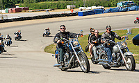 Motorcyclists come around turn two in support of the Boys and Girls Club of the Lakes Region as they take a spin around the oval during the Community Appreciation Parade at NHMS on Saturday morning.  (Karen Bobotas/for the Laconia Daily Sun)