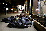 A 10 year old boy sleeps rough under plastic bin bags with friends outside a department store on the streets of Harare in Zimbabwe.