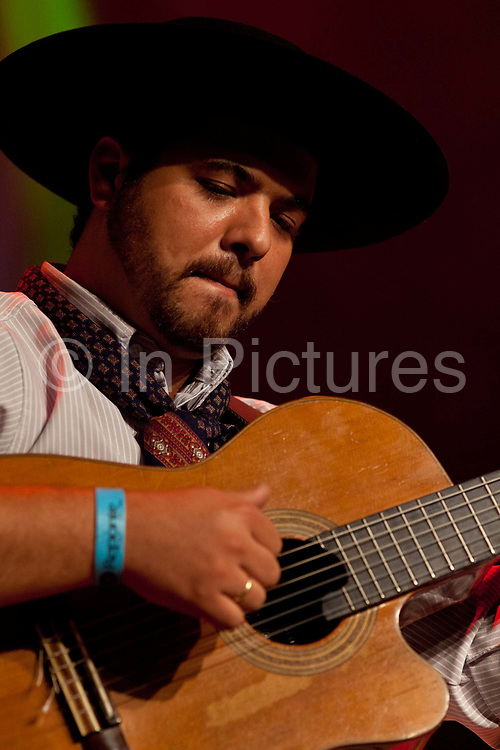 Brazilian Gaucho man in traditional dress playing the guitar on stage, Reponte da Cancao music festival and song competition in Sao Lorenzo do Sul, RIo Grande do Sul, Brazil.
