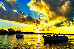 A Golden Sunset Shines Through Big Clouds On The Lake
