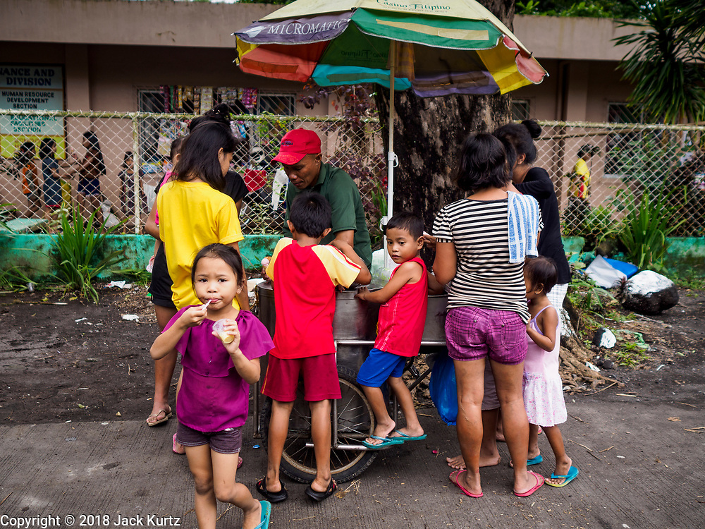 28 JANUARY 2018 - LEGAZPI, ALBAY, PHILIPPINES: People living in the shelter buy ice cream from a Legazpi pushcart vender at the evacuation shelter for people from Barangay (community) Matanag in Albay Central School in Legazpi. People from the community have been in the shelter since Mayon volcano started erupting two weeks ago. There are about 500 families at the shelter, around 2,000 people. More than 80,000 people have been evacuated from communities around the volcano and are living in shelters and camps outside of the evacuation zone. The Philippine government is preparing to house the people for up to three months.      PHOTO BY JACK KURTZ