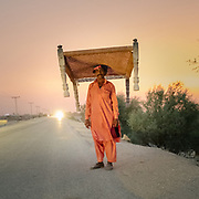 Madan Ali carries his Charpai, a traditionnal woven bed, to a cold area for the night. In the city of Sehwan Sharif