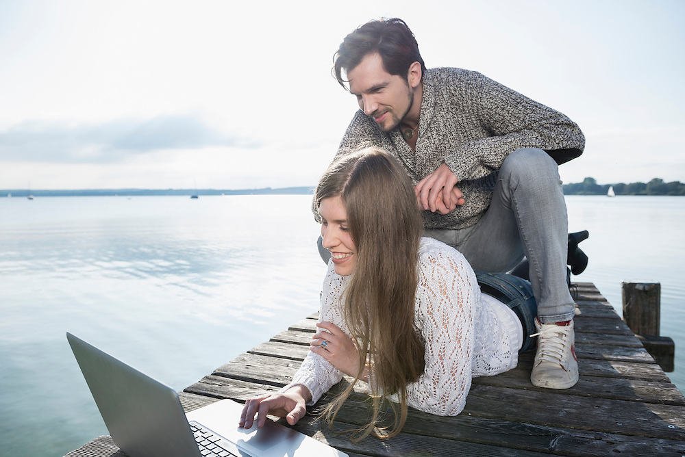Smiling young couple outdoors working laptop