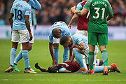 West Ham United midfielder Cheikhou Kouyate (8) is tended to after a tackle during the Premier League match between West Ham United and Manchester City at the London Stadium, London, England on 29 April 2018. Picture by Toyin Oshodi.