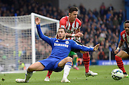 Eden Hazard of Chelsea loses his footing as he is challenged by Jose Fonte, the Southampton captain.. Barclays Premier league match, Chelsea v Southampton at Stamford Bridge in London on Sunday 15th March 2015.<br /> pic by John Patrick Fletcher, Andrew Orchard sports photography.