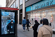On the day that the UK government eased Covid restrictions to allow non-essential businesses such as shops, pubs, bars, gyms and hairdressers to re-open, shoppers pass the Oxford Street Primark where a digital ads message is that London is ready for business, on 12th April 2021, in London, England.