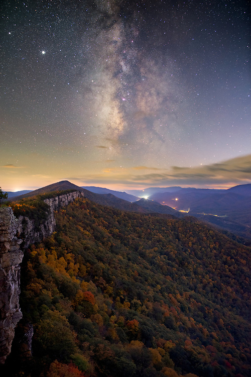 The late autumn Milky Way rises above the sheer cliff walls lining the ridge high atop North Fork Mountain in West Virginia covered in colorful autumn foliage.