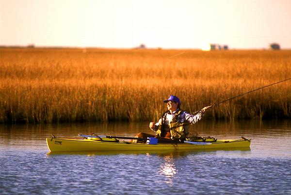 Stock photo of a man sitting in his kayak and casting his rod