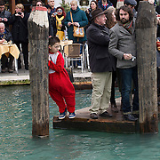 VENICE, ITALY - FEBRUARY 16:  A boy leans on a pole waiting for the passage of the traditional regatta which officially opens the Venice Carnival  on February 16, 2014 in Venice, Italy. The 2014 Carnival of Venice will run from February 15 to March 4 and includes a program of gala dinners, parades, dances, masked balls and music events.  (Photo by Marco Secchi/Getty Images)