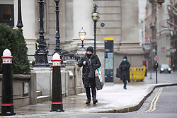 ©️ Licensed to London News Pictures. 08/02/2021. London,UK. A woman is seen commuting  during a snow shower in Bank, central East London. Snow is expected for large parts of the UK and a yellow weather warning is in place in parts of England as Storm Darcy hits the UK. Photo credit: Marcin Nowak/LNP
