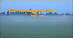 Pilot Rich Davidson heads toward his J-3 cub as fog settles over the Mt. Comfort airport near Indianapolis, IN.