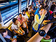 06 DECEMBER 2018 - SAMUT PRAKAN, THAILAND:  Passengers ride in an already full carriage on the new east extension of the BTS Skytrain on the opening day of the extension. The 12.6 kilometer (7.8 miles) east extension of the Sukhumvit Line of the Bangkok BTS Skytrain goes into Samut Prakan, a town east of Bangkok.  The system is now 51 kilometers long (32 miles), including the 12.6 kilometer extension that opened December 06. About 900,000 people per day use the BTS.     PHOTO BY JACK KURTZ