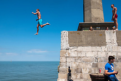 © Licensed to London News Pictures. 12/06/2021. London, UK. Teenagers jump Harbour wall  basking in the sun at Margate Beach in Margate, Kent. The UK is currently experiencing an extended hot weather period. Photo credit: Ray Tang/LNP