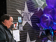"22 APRIL 2016 - MINNEAPOLIS, MN: A man pauses at a memorial to Prince in front of 1st Ave in Minneapolis. Thousands of people came to 1st Ave in Minneapolis Friday to mourn the death of Prince, whose full name is Prince Rogers Nelson. 1st Ave is the nightclub the musical icon made famous in his semi autobiographical movie ""Purple Rain."" Prince, 57 years old, died Thursday, April 21, 2016, at Paisley Park, his home, office and recording complex in Chanhassen, MN.    PHOTO BY JACK KURTZ"