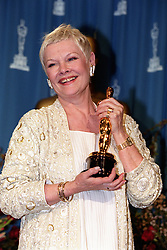 British actress Dame Judi Dench with her Oscar for Best Supporting Actress at the 71st annual Academy Awards in Los Angeles. Dame Judi won the award for her role as Elizabeth I in 'Shakespeare in Love.
