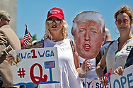 """Veronica Lemoa and Debbie Roberts at an 'End the Shutdown"""" protest in Baton Rouge. LA on April 25, 2020 in Baton Rouge , Louisiana holding a photo of Trump's head and a QAnon sign. A group of a few dozen people who want the restrictions Gov. John Bel Edwards put in place to stop the spread of COVID-19 lifted, held a rally in front of the State Capitol Building on Saterday, before marching to the Governors Mansion where they called on him to end the shut down."""
