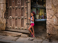 A girl looking out a large wooden gate door revealing a courtyard behind her in Old Havana.