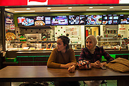 Fatma Uyar (left) and Hayrunnisa (right) work together in a university library. They relax and talk in the Kayseri Forum shopping centre.